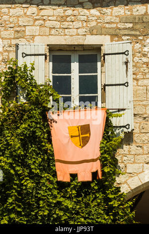 Window with flag on historic Place des Arcades in this lovely south western bastide town. Monflanquin; Lot-et-Garonne; - Stock Photo