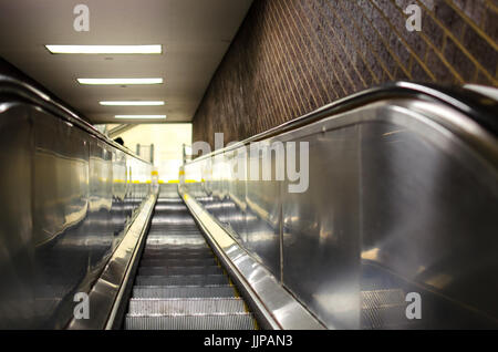 Escalator going down, with a view into a blurry distance - Stock Photo