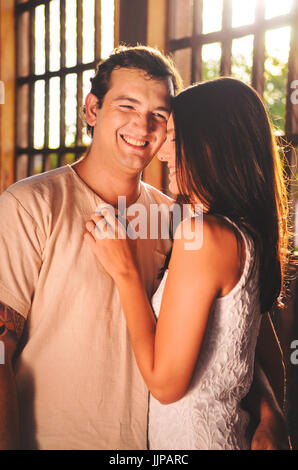 Couple smiling to each other with the nearby body. Warm colors with sunlight through a big window on background. - Stock Photo