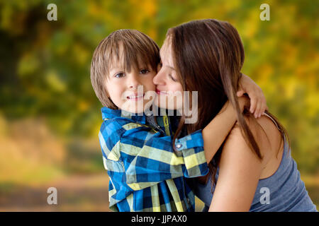 Portrait of beautiful pregnant mother with love hugging her precious son in the park, happy family life - Stock Photo
