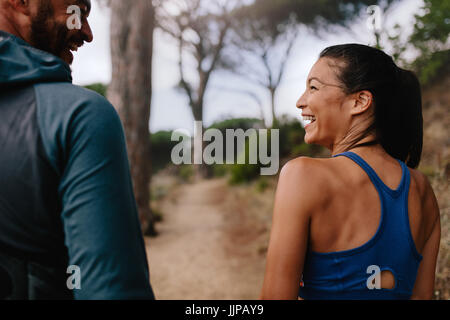 Rear view shot of fit couple smiling mountain trail. Young man and woman walking through country road in morning. - Stock Photo