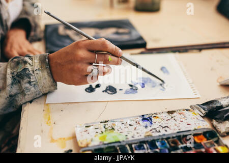 Close up of female artist's hand holding brush and mixing colors on paper. Cropped shot of woman painter working - Stock Photo