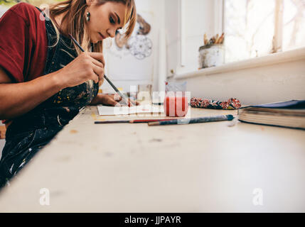 Image of beautiful woman drawing pictures in her workshop. Female artist painting in her studio. - Stock Photo