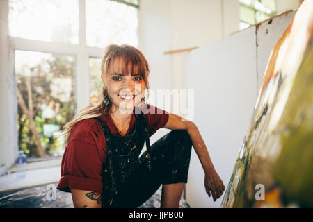 Indoor shot of professional female painter in studio. Woman artist making a painting on canvas in her workshop. - Stock Photo
