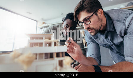 Two male architects in office discussing over house model. Architect working on an architectural model. - Stock Photo