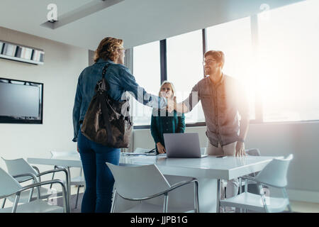 Business people finishing up a meeting. Man shaking hands with female client after successful deal. - Stock Photo