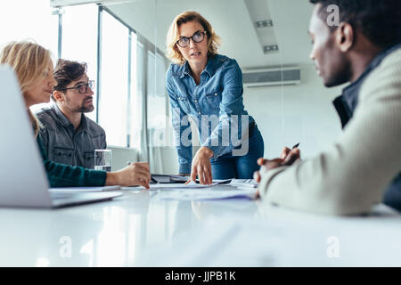 Businesswoman standing and leading business presentation. Female executive putting her ideas during presentation - Stock Photo