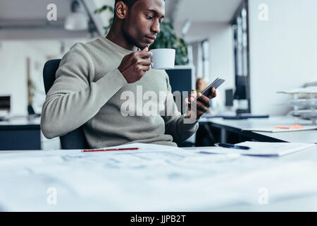 Businessman sitting at office desk having a coffee. Young african man with cup of coffee and smart phone. - Stock Photo