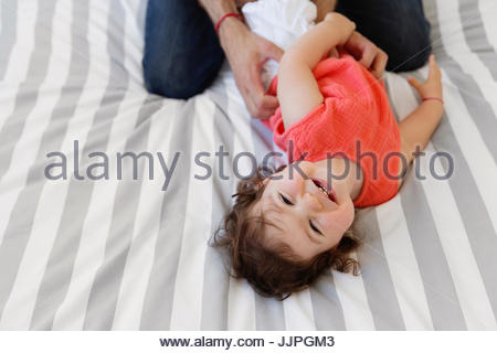 High angle view of man wearing jeans kneeling on bed with stripy duvet, playing with baby girl in red top. - Stock Photo