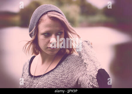 Vintage photo of sad teenager girl at autumn lake - Stock Photo