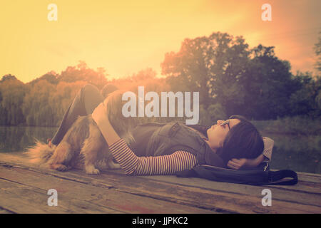 Vintage photo of relaxing woman with her dog on a pier - Stock Photo