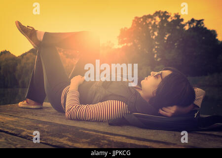 Vintage photo of relaxing woman on a pier - Stock Photo