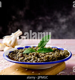a white and blue ceramic plate with spanish arroz negro or black paella, a variation of the seafood paella made - Stock Photo