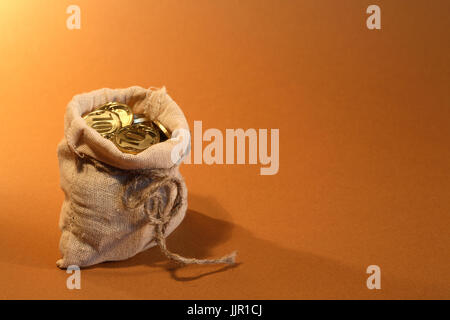 Wealth concept. Open burlap sack full of golden coins standing on nice brown background with free space for text