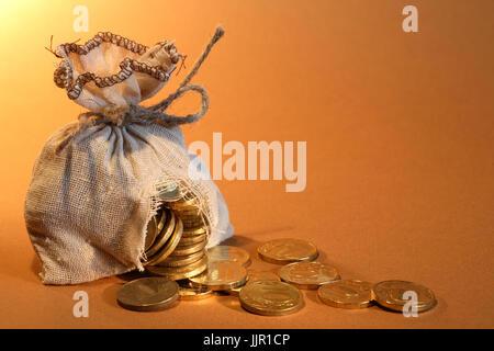Budget concept. Hole-ridden burlap sack with spilled coins