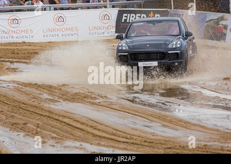 Charity race between a Porsche car and horse takes place on the beach at the British Beach Polo Championships at - Stock Photo