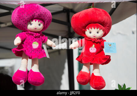 Two dolls on display in market stall. - Stock Photo