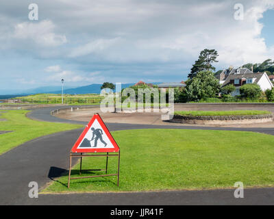 A road works sign men at work misteriously placed in a public park where thetre are no roads to be seen. - Stock Photo