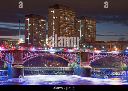 Night photograph taken from the Albery Bridge in Glasgow looking over to the illuminated Pipe Bridge and tidal weir - Stock Photo