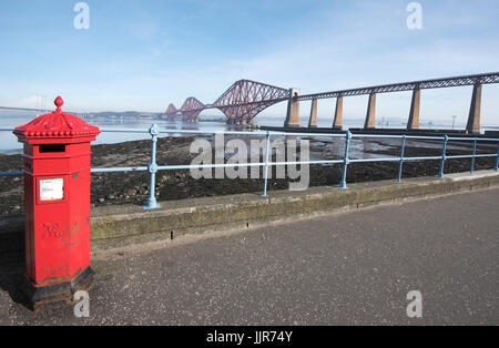 Red post box in South Queensferry with the iconic Forth Bridge in the background. - Stock Photo