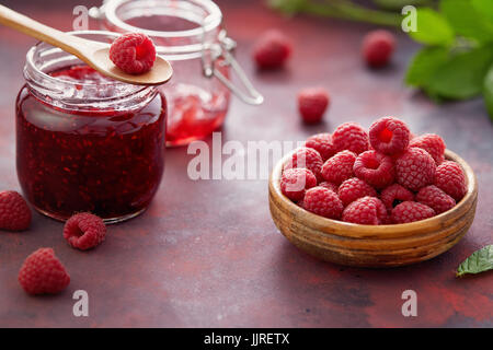 Fresh raspberries and a jar of raspberry jam. - Stock Photo