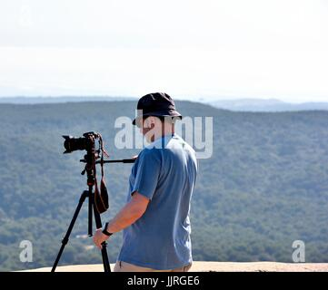 Man using SLR dIgital camera on a tripod - Stock Photo