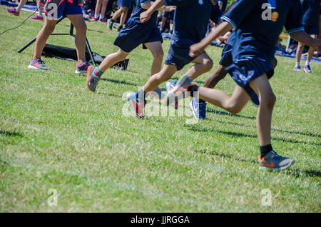 The legs of children competing in a race at school sports day. - Stock Photo