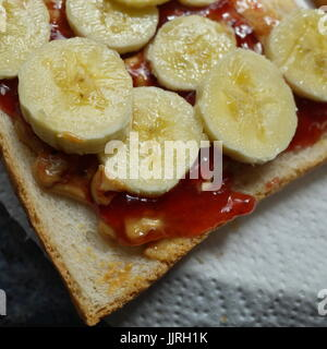 Banana slices, jam and peanut butter on toasted bread - Stock Photo