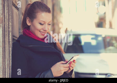 Woman smiling holding a mobile phone standing outdoors next to her new car texting. - Stock Photo