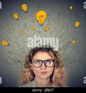 Thoughtful woman in glasses with many ideas light bulbs above head looking up isolated on gray wall background. - Stock Photo