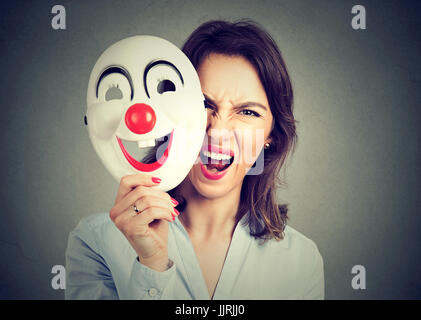 Portrait angry screaming woman taking off happy clown mask isolated on gray wall background. Negative human emotions - Stock Photo