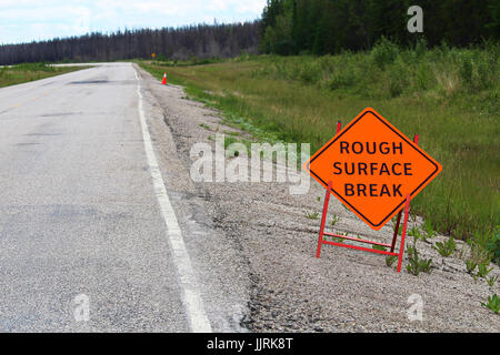 An orange rough surface break sign with a road into the distance. - Stock Photo