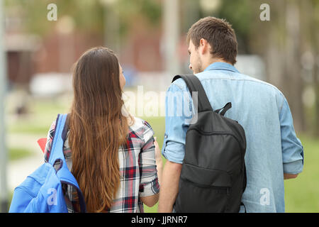 Rear view portrait of two students carrying bags walking and talking in a park - Stock Photo