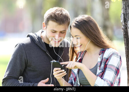 Two friends listening music together and selecting songs in a smart phone outdoors