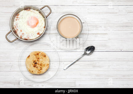 Fried egg, coffee and arepa on wooden white table - Stock Photo