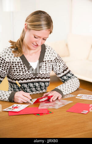Woman writing christmas postcards - Stock Photo