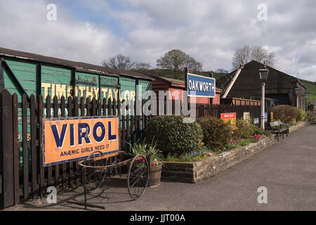 View of old wagons, adverts, cart, gas lamps & deserted platform at quaint, historic Oakworth Station - Keighley - Stock Photo