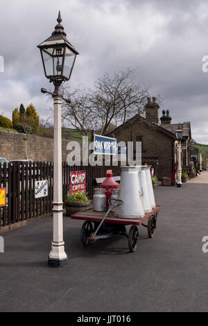 View of old gas lamp & milk churns on cart, on platform at quiet, quaint, historic Oakworth Station - Keighley and - Stock Photo