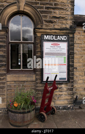 View of red porters' trolley by train times poster on platform at quaint, historic Oakworth Station - Keighley & - Stock Photo