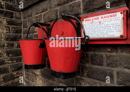 View of 2 old red & black fire buckets hanging on platform wall at quaint, historic Oakworth Station - Keighley & Worth Valley Railway, England, UK.
