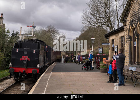 Steam locomotive, BR (Midland Railway) 4F 0-6-0 43924, leaving station, viewed by people on platform - Keighley - Stock Photo