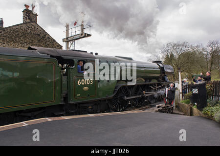 People & iconic steam locomotive LNER Class A3 60103 Flying Scotsman puffing smoke on tracks - Keighley and Worth - Stock Photo