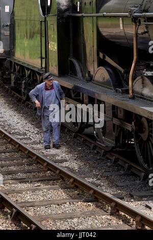 Train driver walks on tracks by steam locomotive, BR (Midland Railway) 4F 0-6-0 43924, at station - Keighley and - Stock Photo