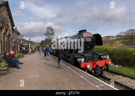 People on platform watch & wave at driver (iconic steam locomotive engine 60103 Flying Scotsman) at station - Keighley - Stock Photo