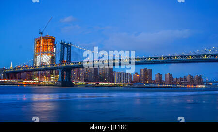 Brooklyn Bridge and NYC Skylinet night with reflection of  the skyline on East River - Stock Photo