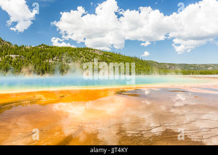 Clouds reflected in the the vivid rainbow colors of the Grand Prismatic Spring in Yellowstone National Park, Wyoming - Stock Photo