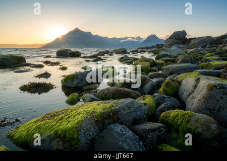 Nice sunset across rocky Elgol beach, on the Scottish Isle of Skye, with a view towards the Black Cuillin mountain - Stock Photo