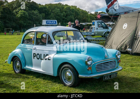 Man sitting in vintage Morris Minor police car, with couple taking a photo, Wheels and wings family day 2016, East - Stock Photo