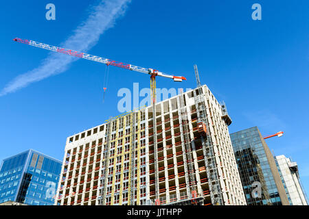 Low angle view of a concrete building under construction between glass buildings with a red and white tower crane - Stock Photo