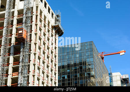 Low angle view of a glass building between two concrete buildings under construction with a red tower crane against - Stock Photo